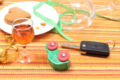 Car key and overturned model vehicle with glass of wine Stock Photo