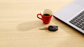 Car key and Red coffee cup and labtop on wood table backgrounds royalty free stock photos