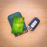 Car key with remote control and credit card. On the wooden table surface stock image