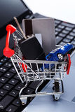 Car and key in shopping trolley. Above laptop keyboard Stock Image