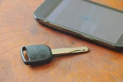 Car key and smart phone opened map on table Stock Images