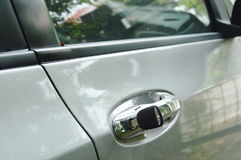 Car key stabbing in handle hole for open door Stock Photos