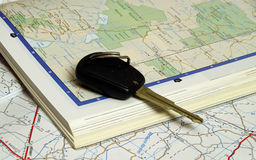 Car key on two open map books Royalty Free Stock Images