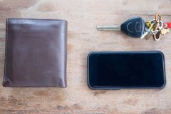 Flat lay car key, wallet and  smartphone. Car key, wallet and  smartphone on wood background, flat lay top view background Royalty Free Stock Image