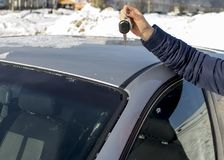 Woman`s hands holding the car key. Car key in woman`s hand with car in background and sunlight Stock Photos