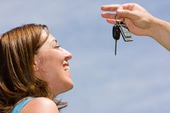Car keys. Hand with car keys and happy woman on blue sky background Stock Photo