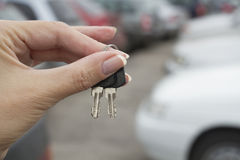The car keys on the background of the Parking lo. The car keys on the background of the Park in warm weather Royalty Free Stock Photography