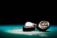 Car keys on blue, reflective table stock photography