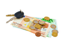 Car keys and coins on euro banknotes. Isolated on white background royalty free stock photography