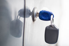 Car keys covered by snow. Blue car keys  covered by snow stuck in door Royalty Free Stock Photography