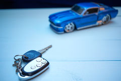 Car keys on a desk with toy car Royalty Free Stock Images