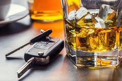 Car keys and glass of alcohol on table. stock images