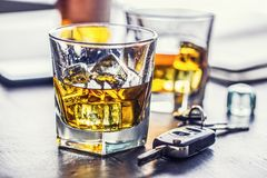 Car keys and glass of alcohol on table in pub or restaurant royalty free stock photography