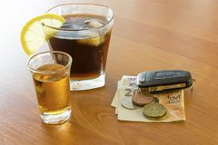 Car keys laid on the bar beside cocktail and whiskey. Whiskey and cocktail at the bar. Alcoholic glasses and car keys. Do not drink alcohol while driving stock photo