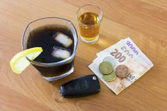 Car keys laid on the bar beside cocktail and whiskey. Whiskey and cocktail at the bar. Alcoholic glasses and car keys. Do not drink alcohol while driving stock images