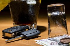 Car keys laid on the bar beside cocktail and whiskey. Whiskey and cocktail at the bar. Alcoholic glasses and car keys. Do not drink alcohol while driving royalty free stock images