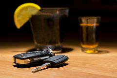 Car keys laid on the bar beside cocktail and whiskey. Whiskey and cocktail at the bar. Alcoholic glasses and car keys. Do not drink alcohol while driving royalty free stock photography
