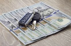 Car keys and money dollars on a wooden background savings stock photos