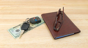 Car keys on money with wallet and sunglasses Stock Image