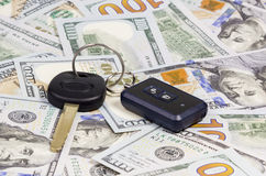 Car keys over dollar. Car keys with remote control alarm located on the hundred dollar banknotes Stock Photo