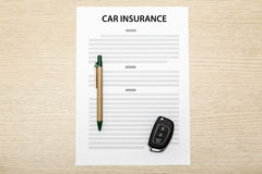 Car keys and pen laying on a blank of insurance. Royalty Free Stock Image