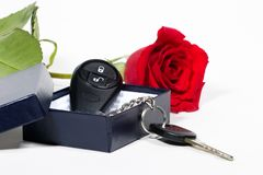 Car keys and roses bouquet. Beautiful scarlet roses bouquet and car keys in box as a Valentine day gift royalty free stock image