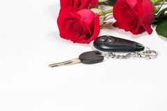Car keys and roses bouquet present. Beautiful scarlet roses bouquet and car keys as a Valentine day gift royalty free stock photos