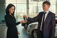 Car keys. Car salesman the men in the jacket hands over the keys to the beautiful client to the girl in the car dealership stock image