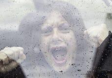 Car kidnapped woman. Sad woman behind wet glass car Stock Photos