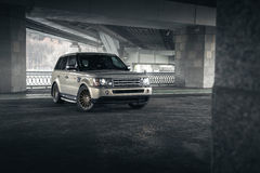 Car Land Rover Range Rover stand under bridge in Moscow city at daytime Stock Photos