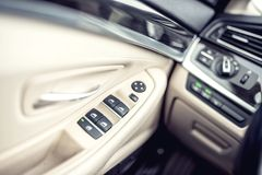 Car leather interior details of door handle with windows controls and adjustments.. Car window controls of modern car Stock Photography