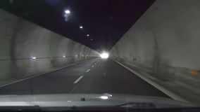 Car leaves the tunnel and drives near mountains stock video