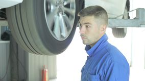 The car is on the lift for diagnosis. The master listens to diagnose the bearings in the wheel stock video
