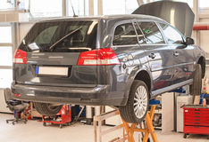 Car on lift in garage. Royalty Free Stock Photo