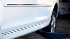 Car Lift Lifting White Car Prepare to Repair. At the Garage stock footage