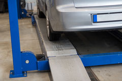 Car on lift at repair station Royalty Free Stock Image