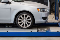 Car on lift at repair station Stock Photos
