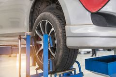 Car on lift to repair suspension to change motor oil and maintenance repair. At service station Royalty Free Stock Image