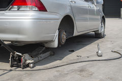 Car lifted by a car jack for wheel replacement in a car shop Royalty Free Stock Images