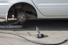 Car lifted by a car jack for wheel replacement in a car shop Stock Photography