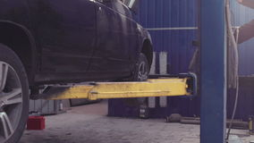 Car lifted on elevator. Black car lifted on elevator in workshop stock footage