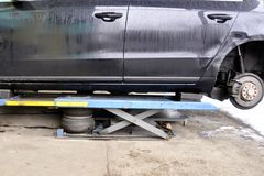 The car lifted by a pneumatic jack, wheel replacement royalty free stock photos