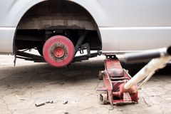 Car lifted with red hydraulic floor Jack for trie replacement Stock Image