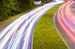 Car light streaks in green environment. A colorful representation of the fast transportation of the modern technological society Royalty Free Stock Photography