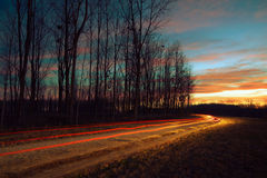 Car light trails by the forest Stock Images