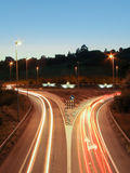 Car light trails on the road and paper boats in a roundabout. Car light trails on the road at night and illuminated paper boats in a roundabout in background Royalty Free Stock Photography