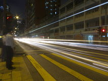 Car Light Trails at Street Crossing. Light trails at a street crossing as people wait to cross the street Stock Photos