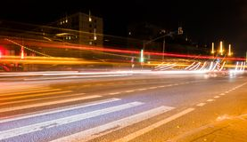 Car light trails on the street near road bridge, people walking in fast motion, night street background Royalty Free Stock Images