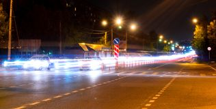 Car light trails on the street near road bridge, people walking in fast motion, night street background Stock Images