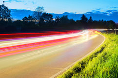 Car light trails in suburban area. A juxtaposition of the calm of the nature and the fast pace of the modern world Stock Photos